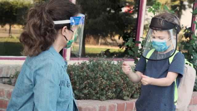 vídeos y material grabado en eventos de stock de profesora que aplica gel desinfectante en las manos de los estudiantes en edad preescolar - parvulario edificio escolar