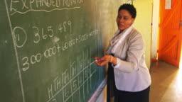Female teacher at the blackboard in front of class 4k