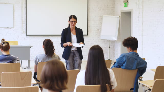 female teacher explaining students in classroom - three quarter length stock videos & royalty-free footage