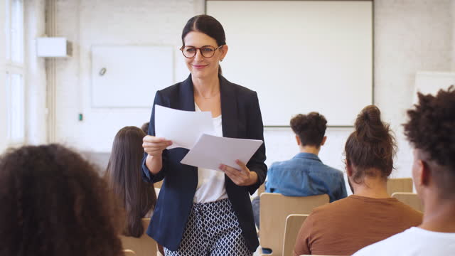 female teacher giving test papers to students - three quarter length stock videos & royalty-free footage