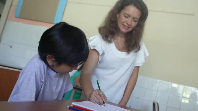 教室で授業を指導する女性教師。 - 消しゴム点の映像素材/bロール