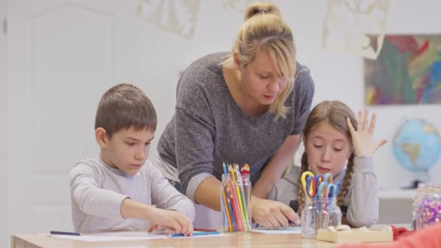 female teacher helping children working at the table - pen holder stock videos & royalty-free footage