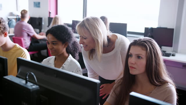 Female Teacher Helping Teenage High School Students Working In Computer Class
