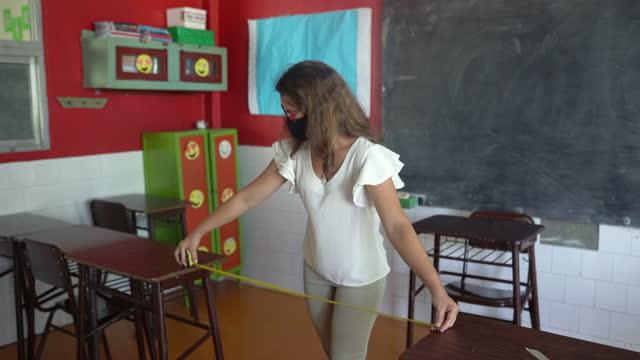 教室の机間の距離を測定する女性教師。新しい正規性。 - 消しゴム点の映像素材/bロール