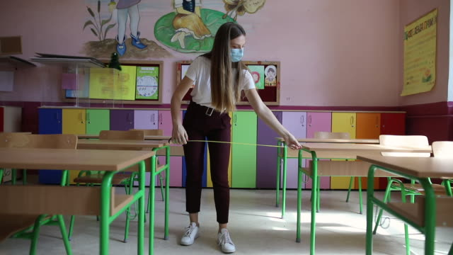 female teacher measuring six feet distance between desks in classroom - instrument of measurement stock videos & royalty-free footage