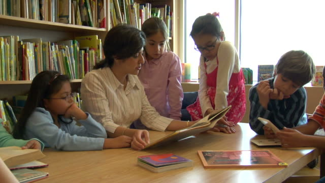 ms, female teacher reading to children (6-7, 8-9) in school library - kind im grundschulalter stock-videos und b-roll-filmmaterial