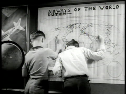 stockvideo's en b-roll-footage met female teacher standing, sixth graders at tables writing, airplane posters bg. boys mapping air routes on map . dramatization: vs boy in class... - fysische geografie
