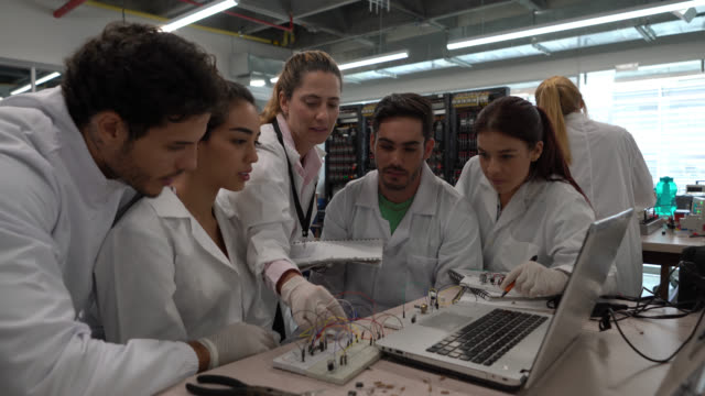 female teacher supervising electrical connections and explaining something to students during a laboratory session at college - lab coat stock videos & royalty-free footage
