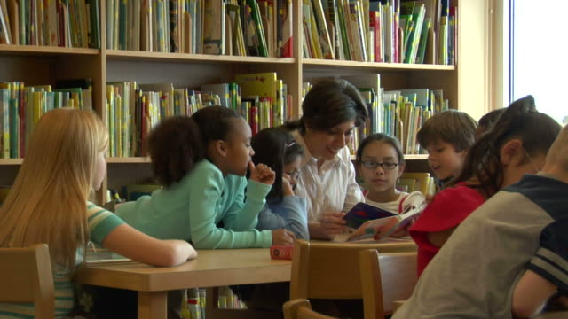 ms, female teacher surrounded by children (6-7, 8-9) reading book in classroom - insegnante video stock e b–roll