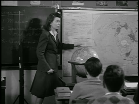 vidéos et rushes de b/w 1944 pan female teacher talking + pointing to maps at front of classroom / educational - enseignante