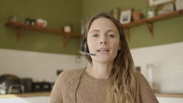 female teacher using headset during video call and looking at camera, working from home at kitchen table during pandemic - webcam stock videos & royalty-free footage
