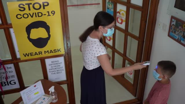 vídeos de stock e filmes b-roll de female teacher using thermometer temperature screening for little students - instrumento de medição