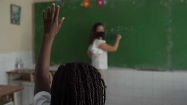 生徒を持つ女性教師は、教室でフェイスマスクを着用しています。コーヴィッド-19 コンセプト - 消しゴム点の映像素材/bロール
