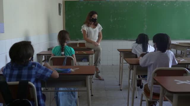 教室で生徒を持つ女性教師。コーヴィッド-19 コンセプト - 消しゴム点の映像素材/bロール