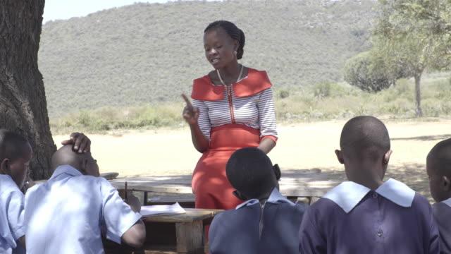 Female teacher with school children. Kenya, Africa.