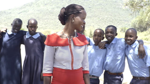 Female teacher with school children. Kenya, Africa.