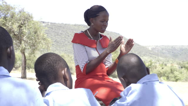 female teacher with school children. kenya, africa. - girls stock videos & royalty-free footage