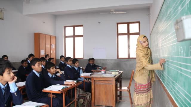 vidéos et rushes de female teacher writing on the blackboard for a class of middle school boys in uniform. no audio - vêtement religieux