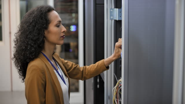 ds female technician checking cable connections in the server room - tecnico video stock e b–roll