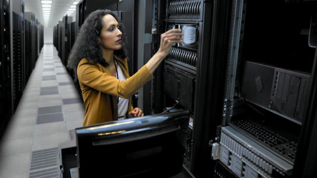 ld female technician inserting hard discs in the server room - tecnico video stock e b–roll