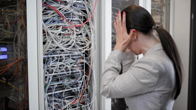 vídeos de stock e filmes b-roll de female technician upset about the cable mess in the server rack - emaranhado