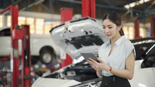 4k female technician using a digital tablet in auto repair shop - repairing stock videos & royalty-free footage