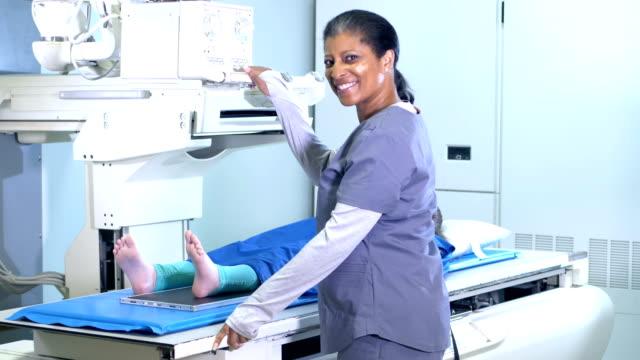 vídeos y material grabado en eventos de stock de tecnóloga femenina tomando radiografía sorda del pie de la niña - radiographer