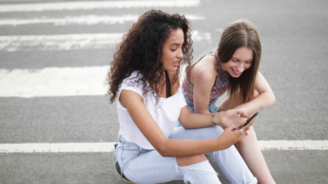 female teenage friends looking at smartphone - 16 17 jahre stock-videos und b-roll-filmmaterial
