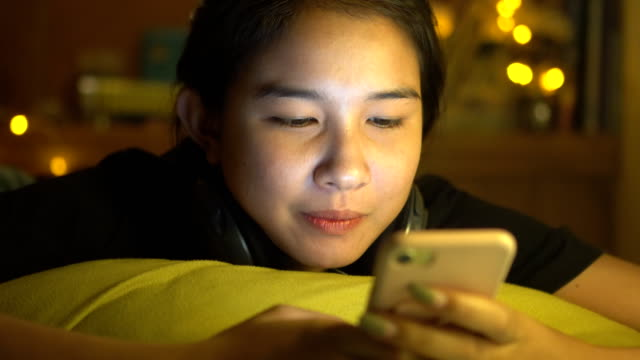 female teenager girl using smartphone in bedroom at night - southeast asia stock videos & royalty-free footage