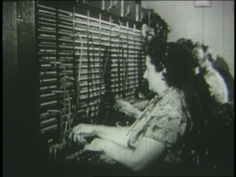 b/w 1951 side view female telephone operator working at switchboard - 電話交換機点の映像素材/bロール