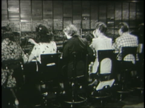b/w 1946 rear view female telephone operators working at switchboard / industrial - customer service representative stock videos & royalty-free footage