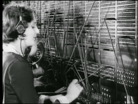 b/w 1925 profile female telephone switchboard operator / newsreel - カスタマーサービス担当者点の映像素材/bロール