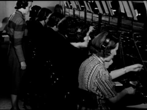 female telephone switchboard operators working on telephone switchboard connecting wires to jacks in panel telephone switchboards switch board... - 電話交換機点の映像素材/bロール