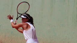 Female tennis player hitting ball on clay court