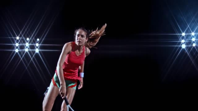 vídeos de stock, filmes e b-roll de slo mo td female tennis player in red dress hitting the serve on black background - tênis calçados esportivos