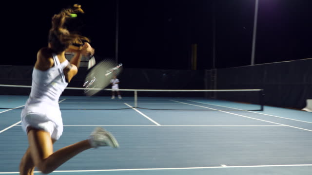 ts female tennis player practicing with male teammate on outdoor court at night - tennis stock videos & royalty-free footage