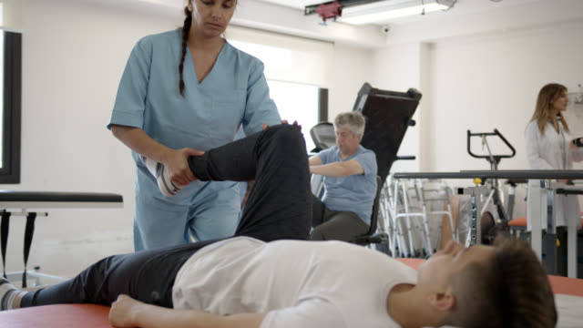 female therapist helping young patient lying down on gurney to stretch his leg while talking to him - physical therapist stock videos & royalty-free footage