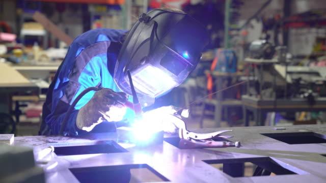 Female TIG soudeur travaillant dans l'atelier