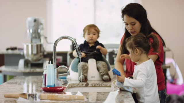 Female toddler washing dishes with her mothers help