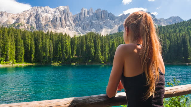 female tourist at lake in dolomites mountains looking at breathtaking view - austria stock videos & royalty-free footage