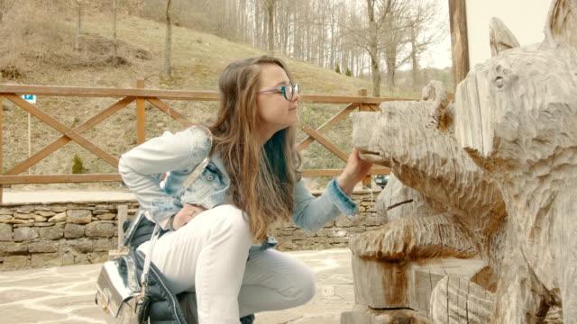 vídeos de stock, filmes e b-roll de turismo feminino verificando estátuas de madeira urso - estátua
