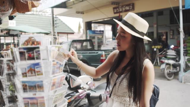 女性観光客はポストカードを選択し、ピッキング - お土産点の映像素材/bロール
