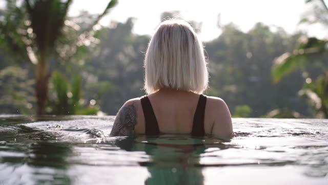 インフィニティプールから熱帯の景色を楽しむ女性観光客 - インフィニティプール点の映像素材/bロール