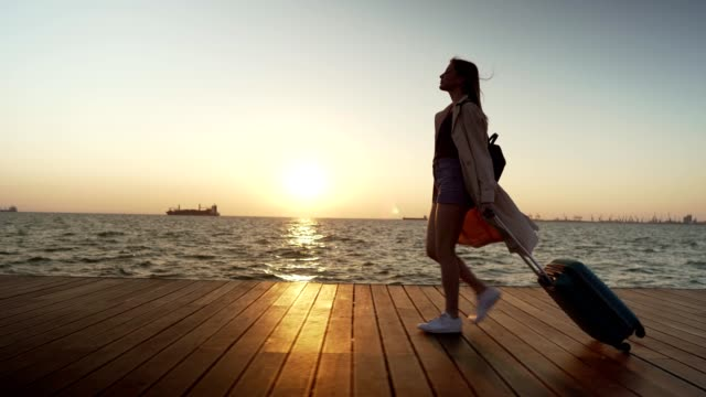 female tourist enjoying the walk by the sea - tracking shot stock videos & royalty-free footage