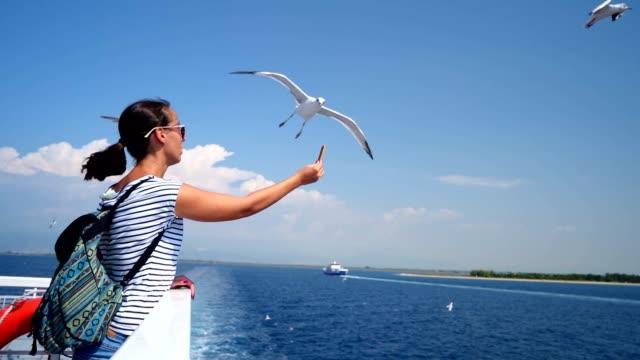 Female tourist feeding seagulls in flight