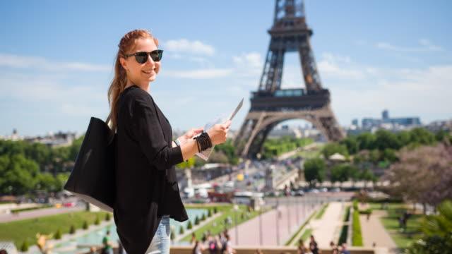 Weibliche Touristen halten Karte von Paris und mit Blick auf Eiffelturm Trocadero stehend
