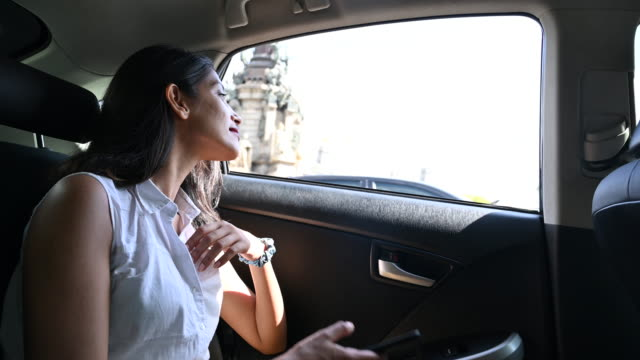 female tourist in backseat of car and checking smart phone - car interior stock videos & royalty-free footage