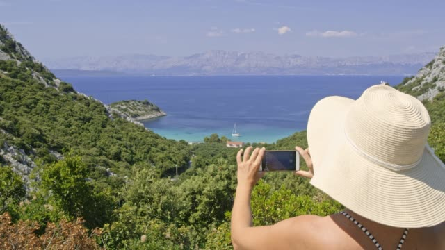 ms female tourist in sun hat with camera phone photographing sunny ocean view,trpanj,croatia - sun hat stock videos & royalty-free footage