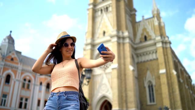vidéos et rushes de touriste féminin effectuant des selfies dans la ville étrangère - serbie