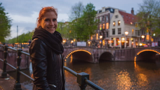 female tourist on vacations in amsterdam, exploring cities nightlife, admiring illuminated bridges over canals - amsterdam stock videos & royalty-free footage